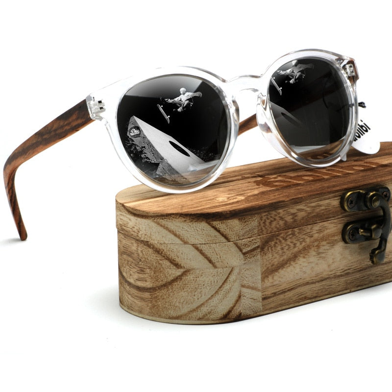 WoodYou Sunglasses resting on the wooden case. Silver frame with Wooden arms and the reflections of a Skateboarders in the lens