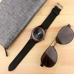 Luxury Wooden watch with leather band placed on a table with a bamboo pair of aviator sunglasses and note book