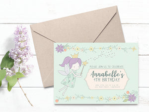 Kraft envelope and child's birthday invitation with fairy princess. Invitation and envelope are sitting on a white wood background with purple lilac flower.
