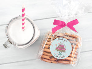 Package of cookies in clear plastic wrap with pink ribbon. Cookie package has pink birthday cake sticker that reads