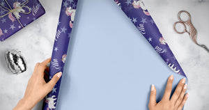 A roll of purple unicorn wrapping paper spread out to wrap presents. You can see female hands holding the paper. There are gold scissors and silver ribbon. There is a wrapped present with twine.