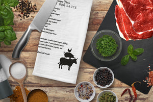 Top view of a BBQ Kitchen towel with various cooking spices, salt and herbs. A butcher knife is near the towel and there is a cutting board with raw beef. Everything is placed on a rustic wood background.
