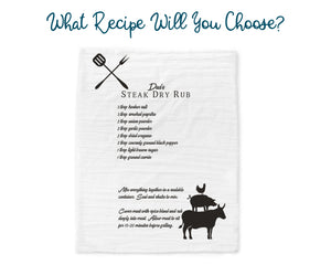 "Another white BBQ towel printed with ""Dad's Steak Dry Rub"" recipe. There are crossed BBQ tool graphics on the top left and silhouettes of a stacked cow, pig and chicken on the bottom right. Text on the picture reads ""What recipe will you choose?"""