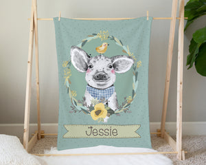 Green blanket with a pig wearing a blue bandana around his neck. The pig has a baby chick on his head and is surrounded by flowers and leaves. The baby's name is shown on the bottom of the blanket. The blanket is hanging up in a living room.