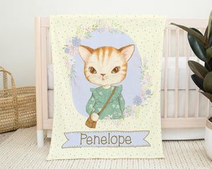Yellow blanket with purple polka dots and the portrait of a cat wearing a green dress and brown purse. Cat is surrounded by flowers and a baby's name is across the bottom. Blanket shown hanging on a crib in a nursery.