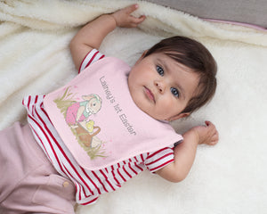 "A baby girl in a striped red shirt and pink pants is laying on a fuzzy blanket wearing a pink Easter bunny bib that says ""Lainey's 1st Easter""."
