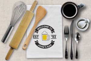 Personalized logo bar towel with beer glass. Bar towel is laying on a linen tablecloth surrounded by cutlery, coffee and kitchen tools. View is from above.