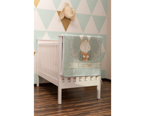 Baby nursery with a crib and green vintage bunny blanket draped over it. The walls of the nursery are painted with green and white triangles and there is a stuffed elephant head hanging on the wall.