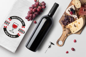 Personalized logo bar towel with red wine graphic. Towel is laying on a table with wine bottle, cork screw, grapes and cheese board. View is from above.