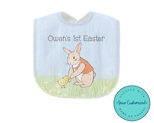 "Baby bib with easter bunny standing in meadow touching a baby chick. Bib has writing ""Owen's 1st Easter""."