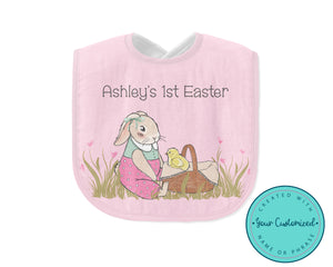 "Pink baby bib with a girl bunny holding a basket with a baby chick. The girl bunny has a ribbon on her ears and is wearing pink bloomers. They are sitting in grass with pink heart flowers. Bib says ""Ashley's 1st Easter"""