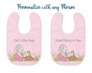 "Bib can be personalized with any phrase. Examples are ""Our Little Peep"" and "" Some Bunny is one"". Two bibs are shown with these text examples."