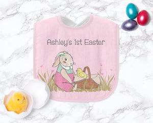 The pink Easter bunny bib is laying on a marble counter with metallic Easter eggs and a fuzzy chick in egg toy.