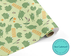 A roll of wrapping paper. The design on the paper is a pattern with green frogs sitting and jumping around lily pads and bugs in a swamp. The paper is personalized with a name in orange.