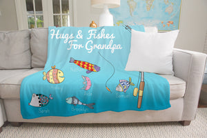 """Hugs and Fishes for Grandpa"" throw blanket with fish and fishing rod draped over sofa in living room. The sofa is grey and has a white throw pillow. The room has windows, a lamp and a map on the wall."