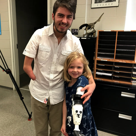 Aaron Westbrook of Form5 Prosthetics Inc. with Maddie trying a prosthetic arm