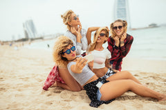 Four blondes on the beach with phones