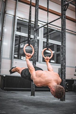 athlete is holding a back lever on rings