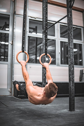 athlete is holding a front lever on rings in a gym