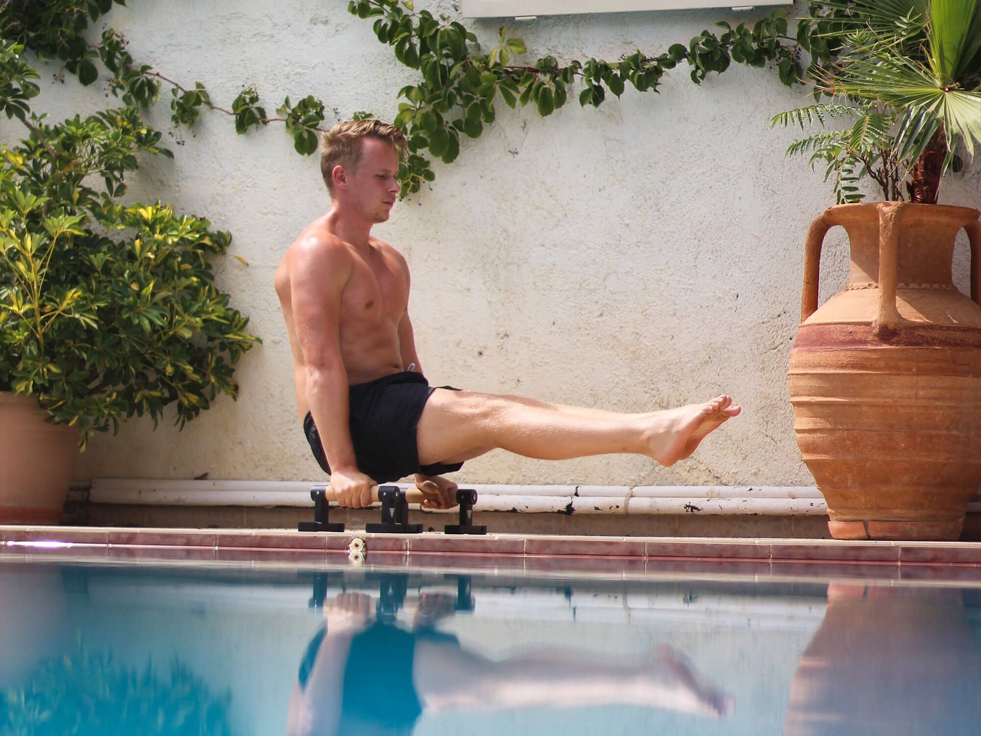 athlete doing l-sit on parallettes at the pool