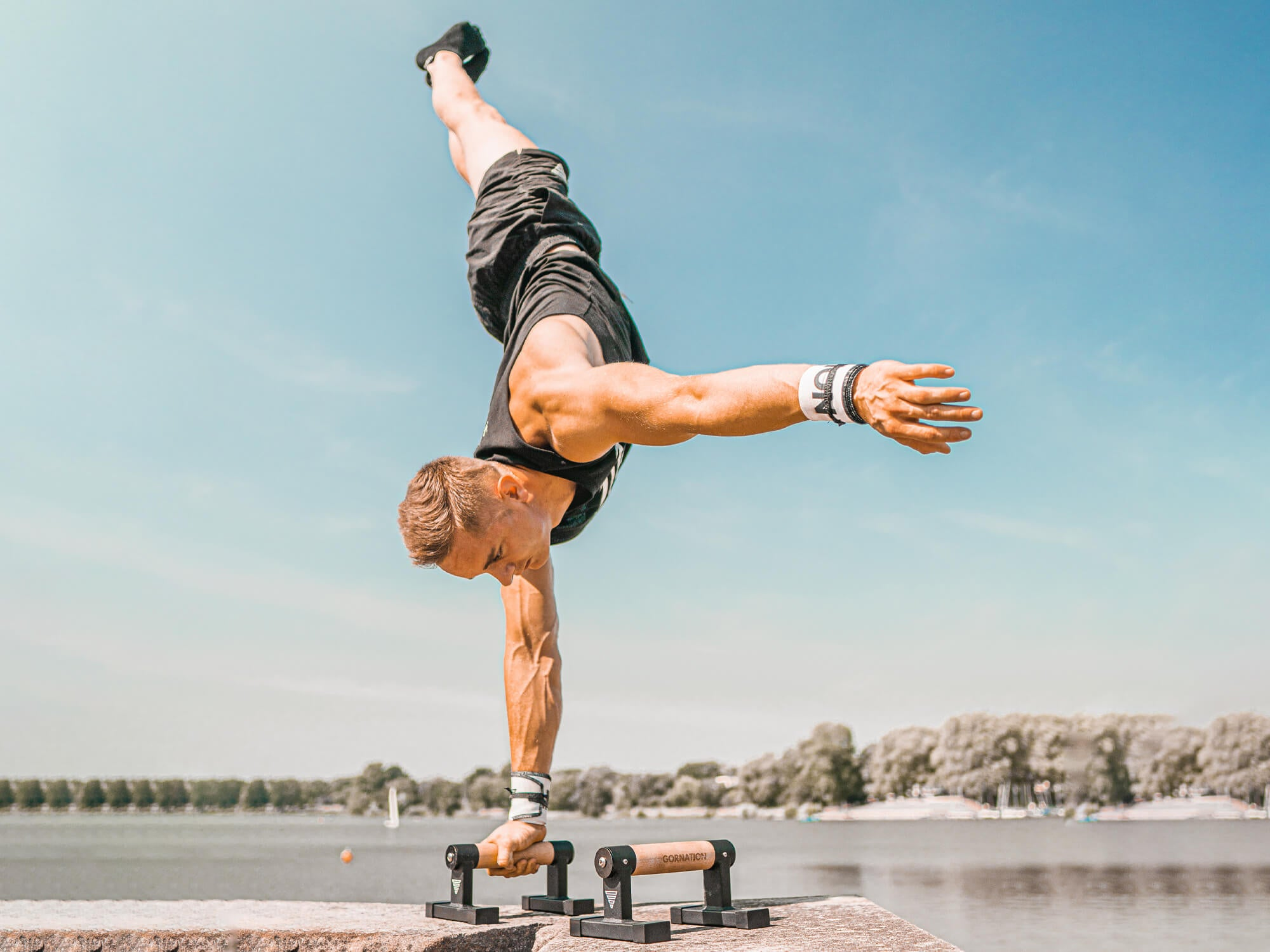 athlete holding a one arm handstand on parallettes