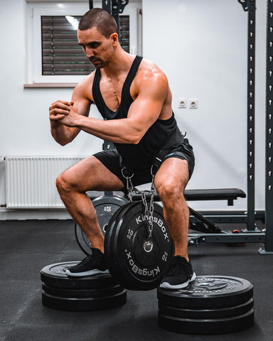 athlete doing squats with dip belt