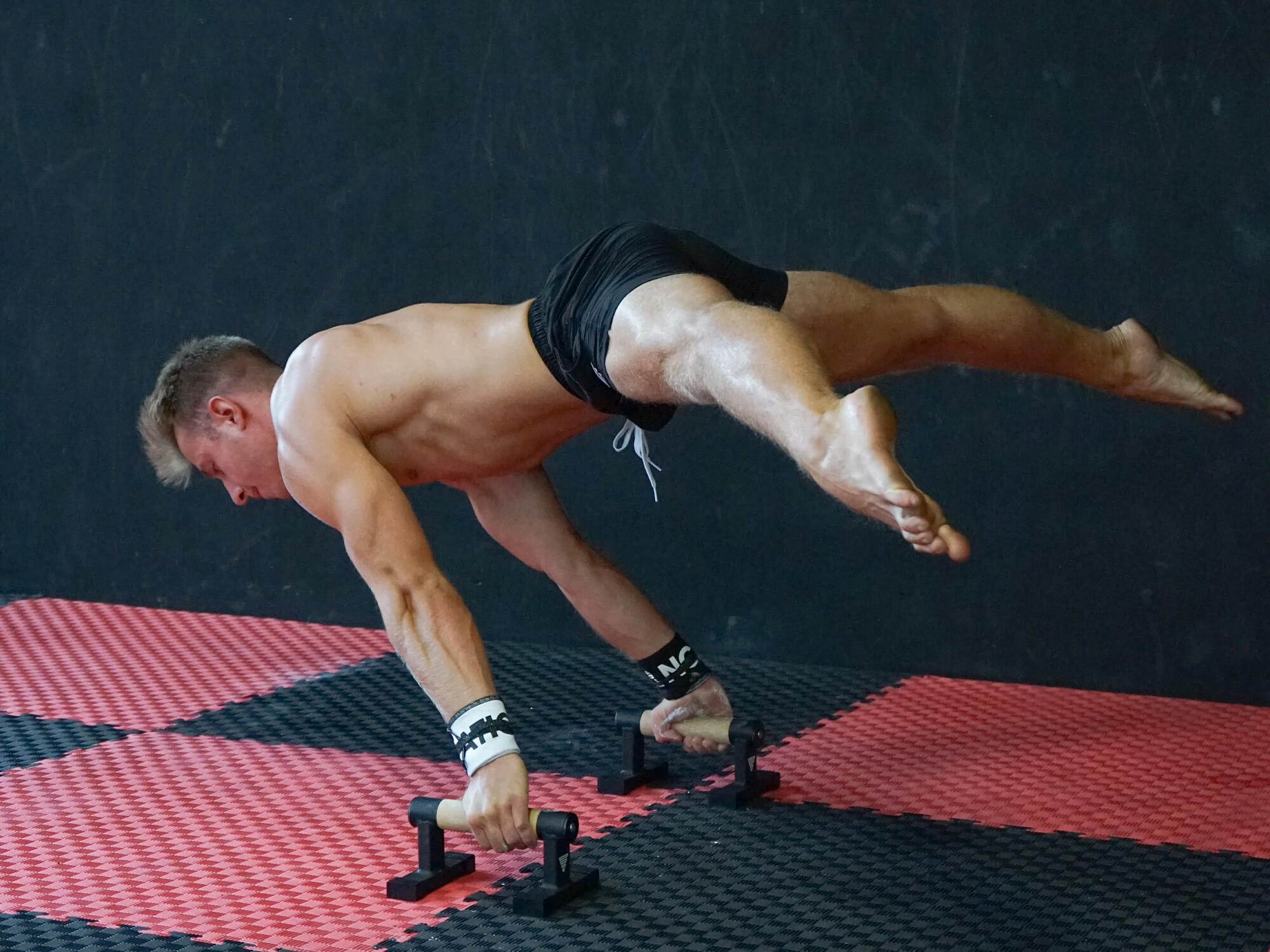athlete holding a straddle planche on parallettes
