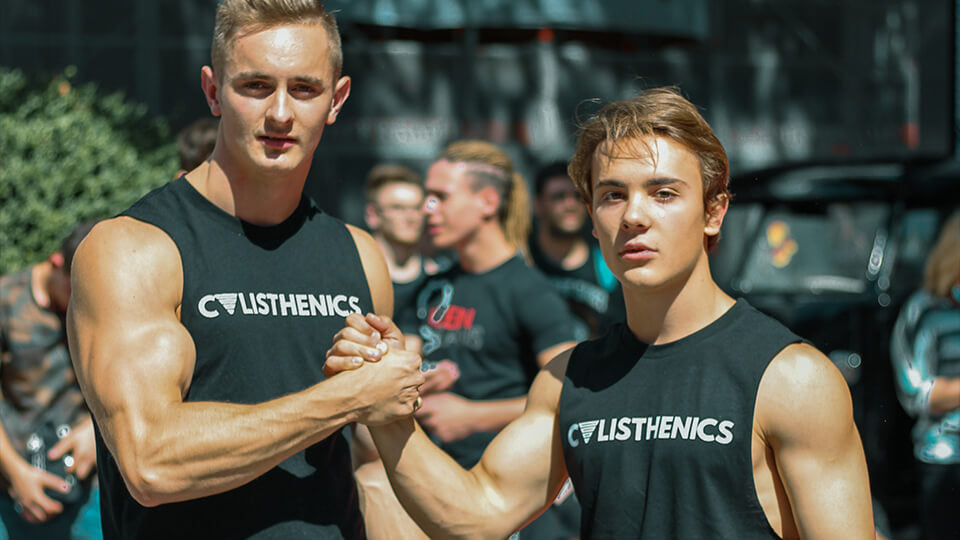 2 calisthenics athletes at a competition with a calisthenics shirt