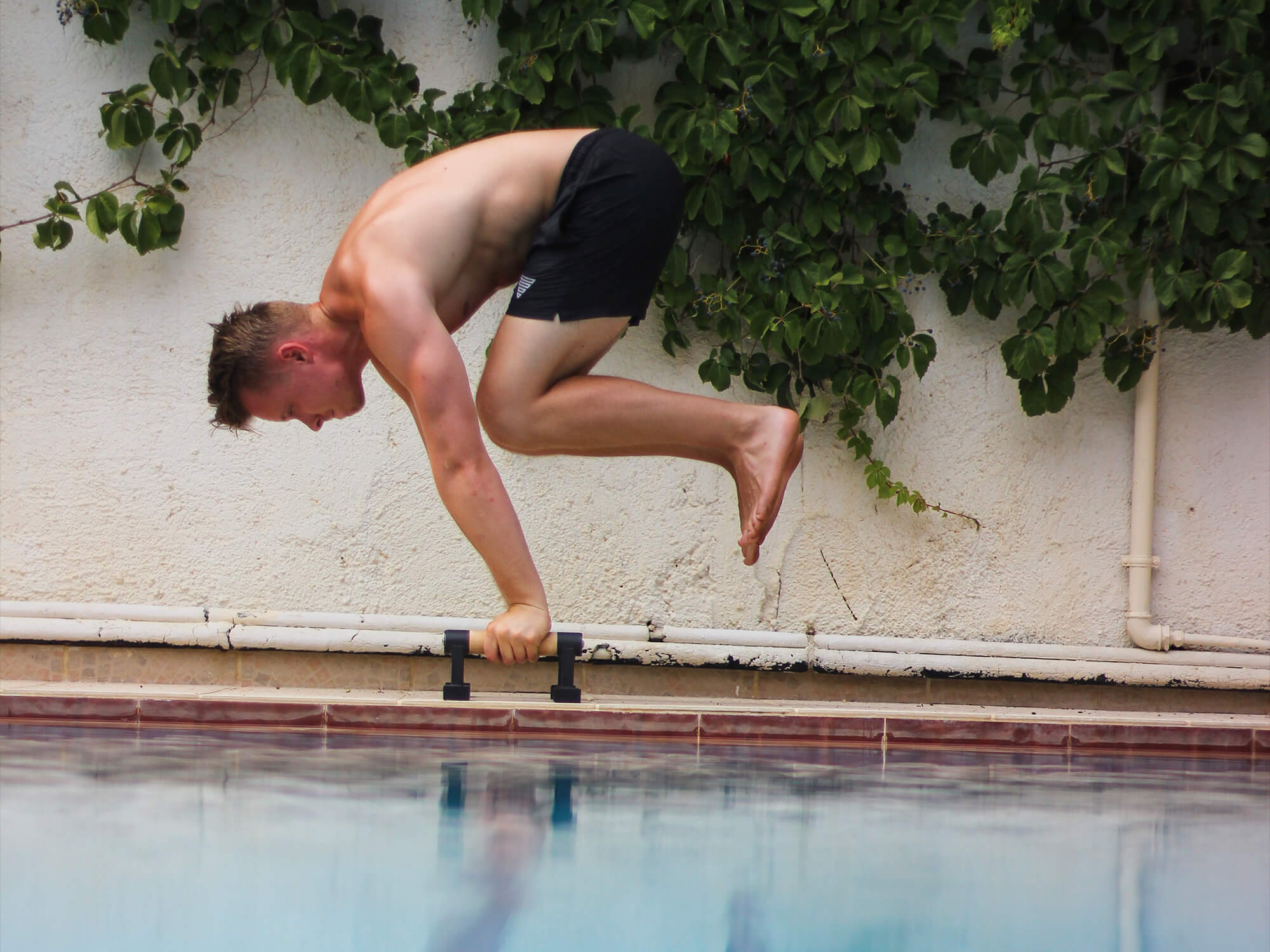 athlete holding a tucked planche on parallettes at the pool