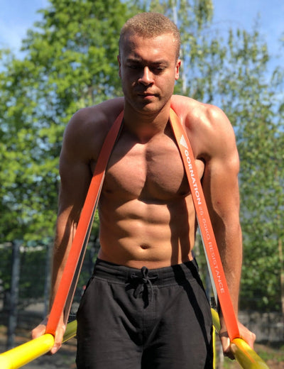 Calisthenics & Street Workout Athlete using Strong Orange Resistance Band, doing Dips