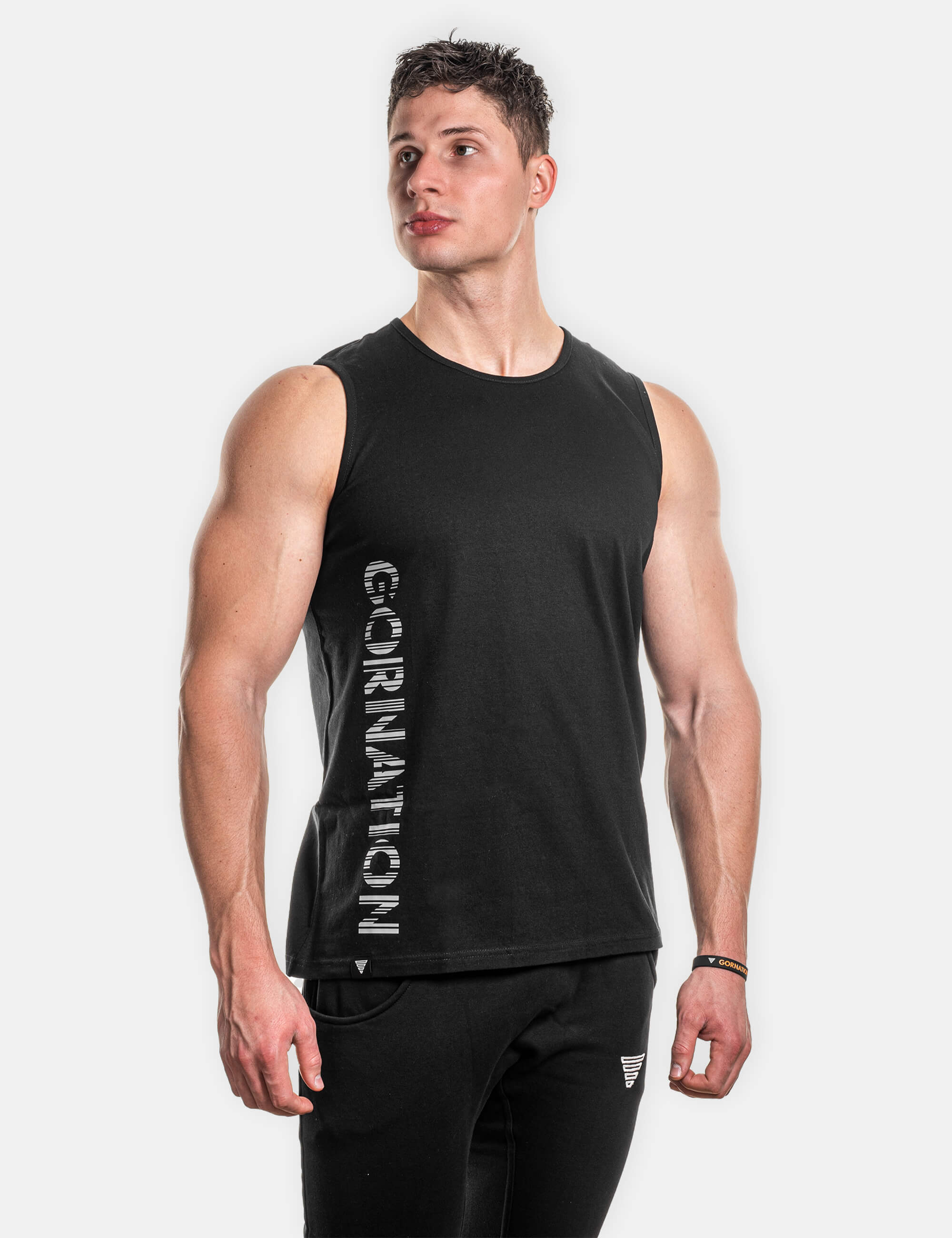 Calisthenics athlete wearing the classic barcode black tank top presenting the gornation brand on the frontside.