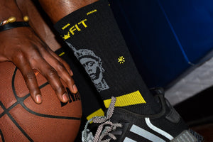 Man holding a basketball and wearing black and yellow socks with an Oduduwa African mask on it.