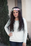A woman wearing a full halo flower crown in her curly hair