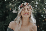 blonde woman laughing wearing a beautiful flower crown outside