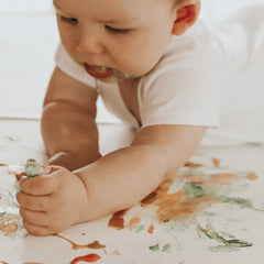 baby having fun with finger paint
