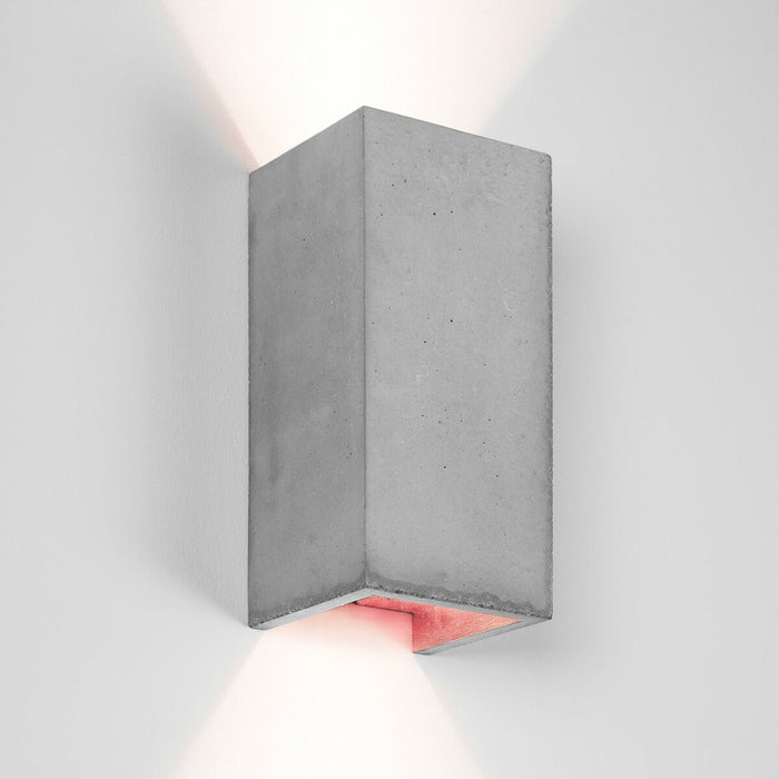 Wall light in rectangular shape made from light grey concrete with a copper coloured inside plating
