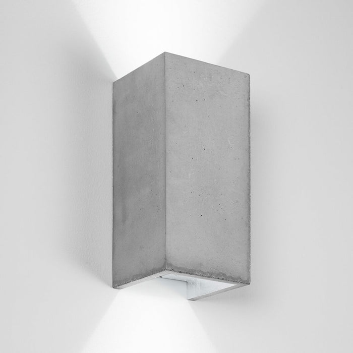 Wall light in rectangular shape made from light grey concrete with a silver coloured inside plating