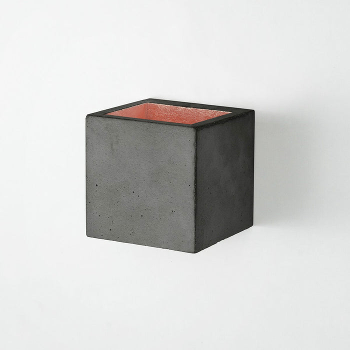 Wall light in 10cm cubic shape made from dark grey concrete with a copper coloured inside plating