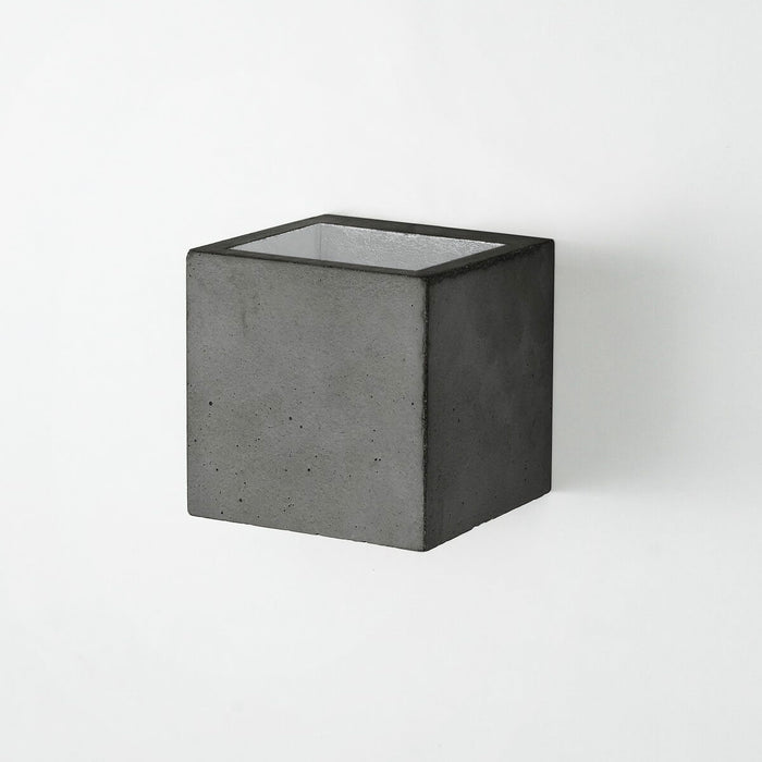 Wall light in 10cm cubic shape made from dark grey concrete with a silver coloured inside plating
