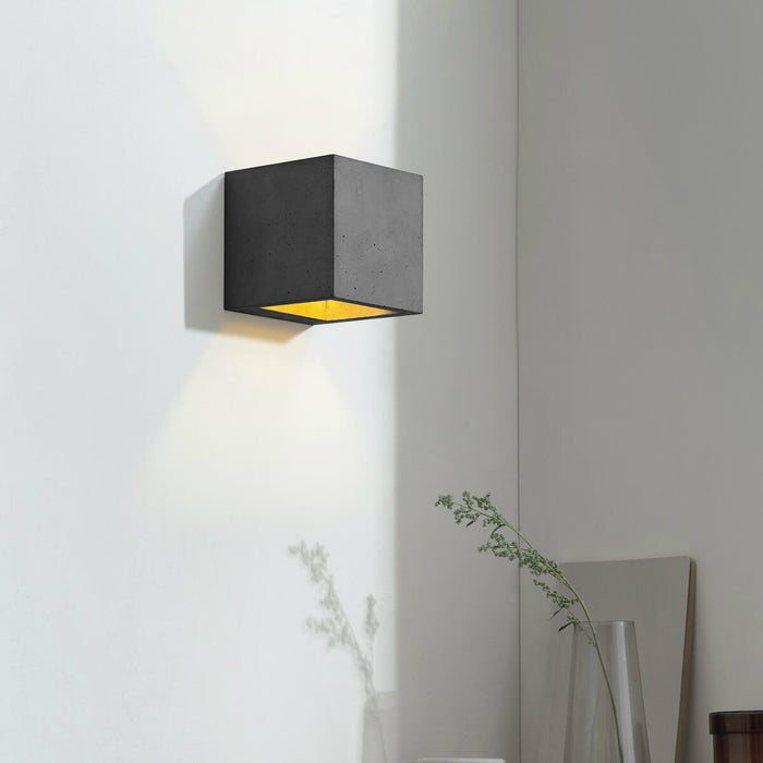 Wall light in 10cm cubic shape made from dark grey concrete with a gold coloured inside plating