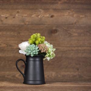 Black antique pitcher filled with an arrangement of faux succulents, roses, and hydrangeas.
