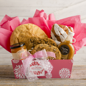 "Kneaders Bakery & Cafe April gift basket with one loaf of Chunky Cinnamon Bread, Kneaders Famous Caramel Syrup, on loaf of Paesano Hearth Bread, Apricot & Pineapple Jam, four gourmet cookies, a ""Bloom Where You Are Planted"" ornament, pink floral box, and pink bows and tissue paper."
