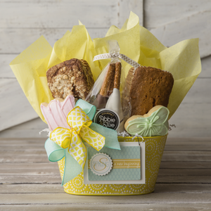 Kneaders Bakery Cafe Spring Gift Basket with one pink tulip and one green butterfly sugar cookie, chocolate and caramel dipped pretzel rods, one loaf of Aloha Coconut Sweet Bread, and on loaf of Banana Crumb Sweet Bread in a yellow basket with yellow tissue paper, a blue and yellow ribbon bow, and a spring ornament.
