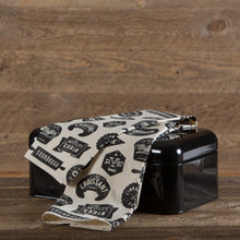 Black and cream tea towel with bakery-inspired print draped over a black metal bread box.