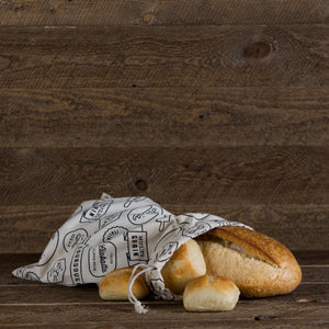 Black and cream cotton bread bag with bakery-inspired print filled with fresh baked bread.