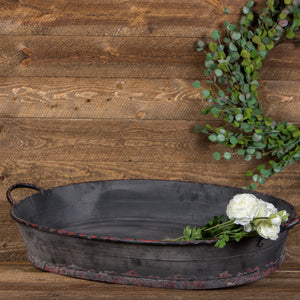 Distressed black oversized oval tray with white faux florals and a magnolia wreath.