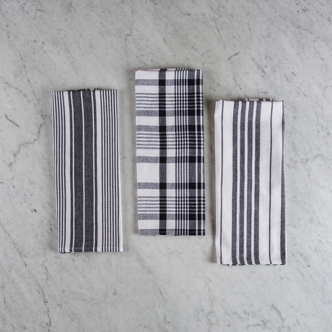 Set of three 100% cotton black and white striped and plaid tea towels folded on a marble surface.