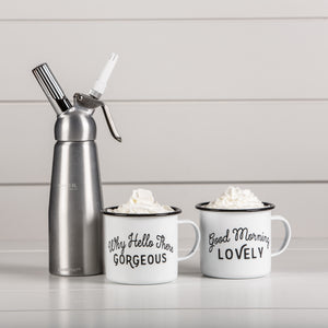 "Two white tin enameled mugs filled with hot cocoa with ""Good morning lovely"" and ""Why Hello Gorgeous"" written in black script. Pictured next to a whipped cream canister."