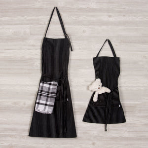 One adult black pinstripe apron with plaid tea towel in the pocket hanging next to a kids size matching apron with a teddy bear in the pocket.
