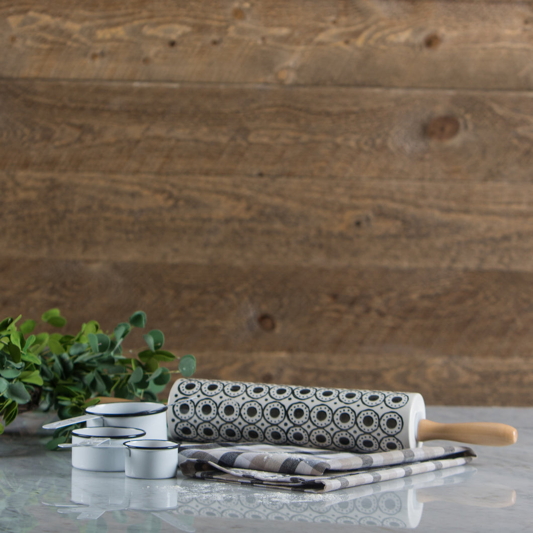 Hand painted black and white stoneware rolling pin with bamboo handles resting on the woven tea towel on a marble surface.